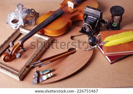 Attributes of arts. Violin, frame, palette, brushes, paints, mask, old camera