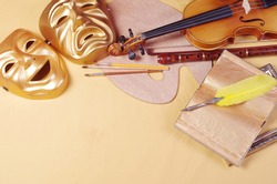 Attributes of the arts. Theatrical masks, art palette, brushes, violin, bow, pipe, fountain pen, book.