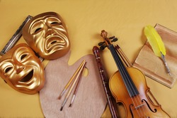Attributes of the arts: Theatrical masks, art palette, brushes, violin, bow, pipe, fountain pen, book.