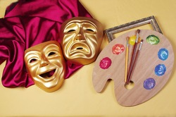 Attributes of the arts. Theatrical masks of tragedy and comedy, drapery, art palette, brushes.