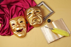Attributes of the arts. Theatrical masks of tragedy and comedy, open book and fountain pen.