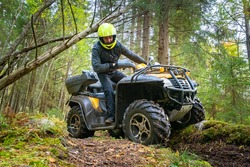 ATV. A man looks at the wheels of a Quad bike. Journey through the forest on a Quad bike. A man rides a Quad bike on the road. Off-road transport. The equipment of the driver of the ATV.