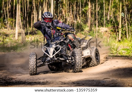 ATV racer takes a turn during a race on a dusty terrain.