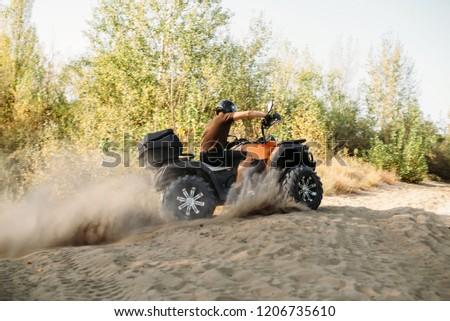 Atv rider in helmet rides on sandy road in forest