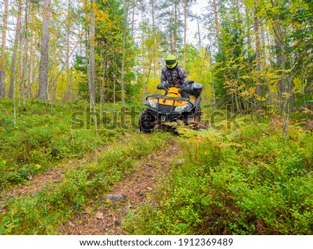 ATV rider rides among tall grass. He travels on quad cycle. ATV rider stands still while riding. ATV rider rides in a yellow helmet. He travels through green forest. Extreme tourism by quad cycle Stock photo ©