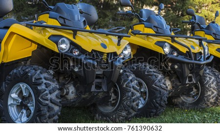ATV yellow are parked in a row on the grass. Stock photo ©