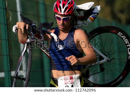 AUCH, FRANCE - SEPTEMBER 8: an unidentified triathlete is carrying his bike on his shoulder in the transition area of the Auch Triathlon, on September 8, 2012 in Auch, France.