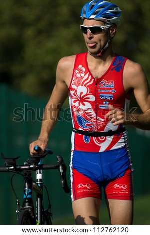 AUCH, FRANCE - SEPTEMBER 8: an unidentified triathlete pushes his bike in the transition area of the Auch Triathlon, on September 8, 2012 in Auch, France.