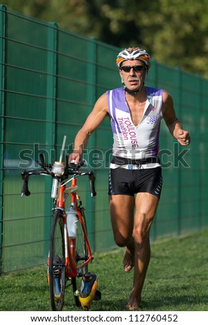 AUCH, FRANCE - SEPTEMBER 8: the triathlete Fabrice Teofili pushes his bike in the transition area of the Auch Triathlon, on September 8, 2012 in Auch, France.