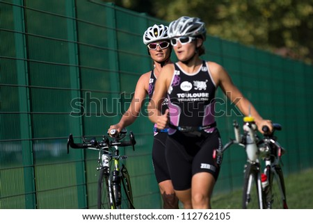 AUCH, FRANCE - SEPTEMBER 8: the triathletes Julie Soriano and Anne Gael Gourdin push their bikes in the transition area of the Auch Triathlon, on September 8, 2012 in Auch, France.