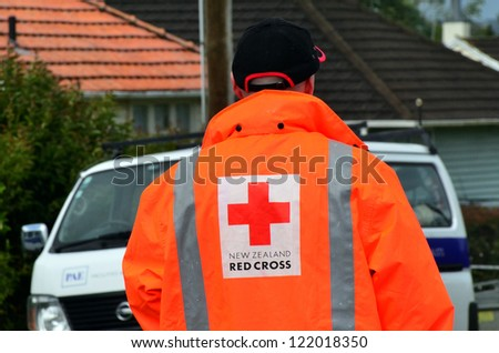 AUCKLAND - DEC 7:Red cross volunteer assist a victim when a rare tornado ripped through Hobsonville in Auckland, NZ on December 7, 2012. It killed 3 and 250 people were left homeless and without power