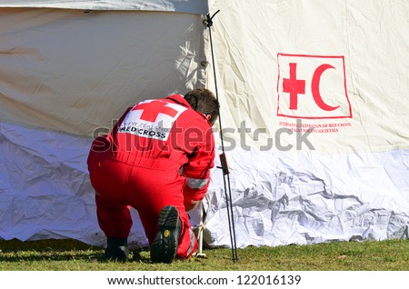 AUCKLAND - DEC 7:Red Cross volunteer build emergency tent when a tornado ripped through Hobsonville in Auckland, NZ on December 7, 2012.It killed 3 and 250 people were left homeless and without power.