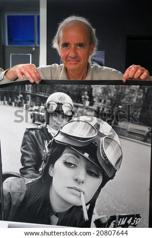 AUCKLAND - MAY 17: German born New Zealand photographer Frank Habicht poses in front of one of his most celebrated 1960's photos, in Auckland, New Zealand on 17 May 2007 - stock photo
