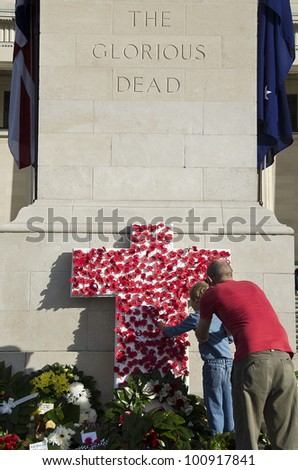 AUCKLAND, NEW ZEALAND - APRIL 25: A father and son place symbolic poppies on a cross at Auckland War Memorial Museum, following an Anzac Day service on April 25, 2012 in Auckland, New Zealand.