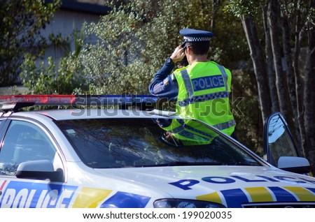AUCKLAND,NZ - JUNE 03 2014:Traffic Police officer pointing his radar gun at speeding traffic.Traffic Police Monitor traffic to ensure motorists observe traffic regulations and safe driving procedures.