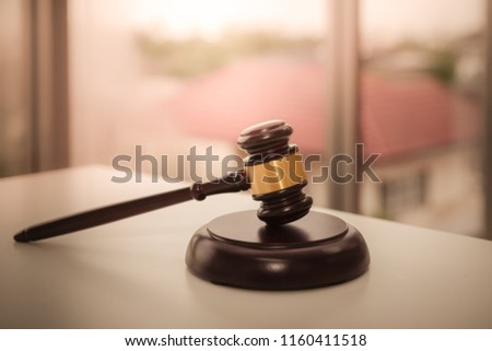 Auction wooden hammer bid sale on the table for law and justice with house background concept