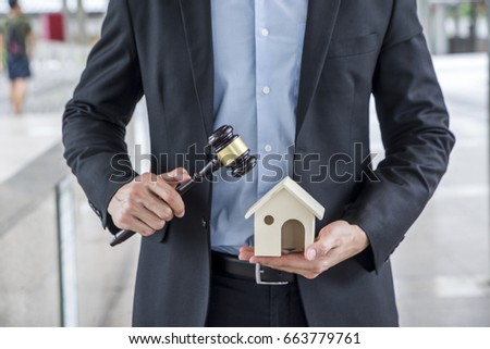 Auctioneer knocking down a property sale holding a model house as he holding gave in hand, or a knocking down or judge mediating in a property dispute in court auction house concept
