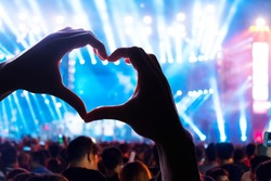 Audience at live music concert Show a heart shaped hands and power of crowd