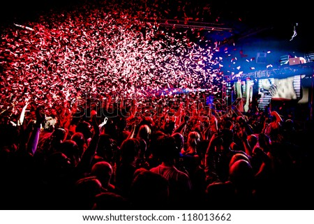 Audience Crowd Silhouette Confetti Explosion While Dancing to DJ Pete Tong at Cream Nightclub Party. Nightlife Lazer Show Hands In Air with Confetti - stock photo