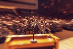 Audience in hall during graduation ceremony. Microphone and stand in front. Concept of graduation, audience or stage fright. Radial zoom effect defocusing filter applied, with vintage instagram look.