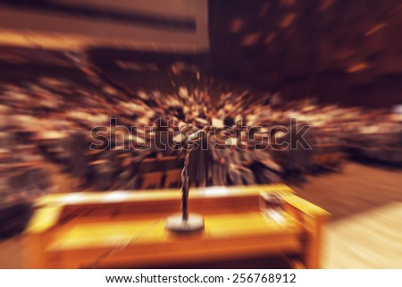 Audience in hall during graduation ceremony. Microphone and stand in front. Concept of graduation, audience or stage fright. Radial zoom effect defocusing filter applied, with vintage instagram look. Stock photo ©