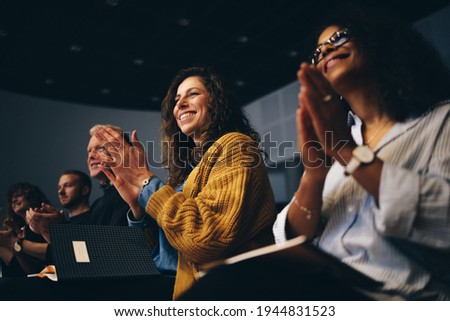 Audience listening to the speech and clapping hands. Group of business people attending a convention applauding during the forum.