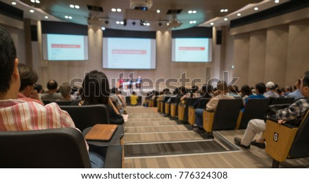Audience view, speaker speech on stage with LED projector screen. Business conference presentation in hall, seminar meeting room.  People listening talk show.  Education  and business concept #776324308