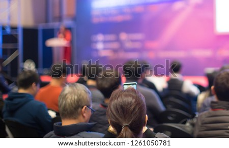 Audience Watching a Presentation. Business. Female Presenter on Stage Giving Talk to Crowd of People. Woman Speaker at  Investor Pitch Conference.  Defocused Blurred Presenter During Conference.