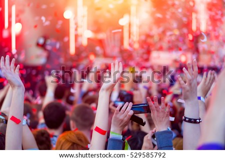 Audience with hands in the air at summer music festival. Fun concert party disco with blurred light background. Hands in the crowd at music festival. Night entertainment, music, happy, summer party