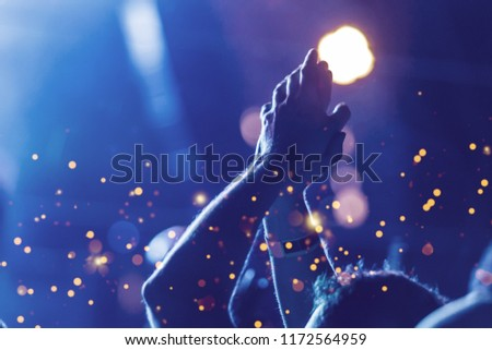 Audience with hands raised at a music festival and lights streaming down from above the stage. Soft focus, blurred movement. #1172564959