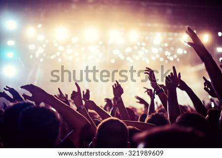 Shutterstock Audience with hands raised at a music festival and lights streaming down from above the stage. Soft focus, high ISO, grainy image.