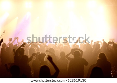 Audience with hands raised at a music festival and lights streaming down from above the stage. Soft focus, high ISO, grainy image. #628519130