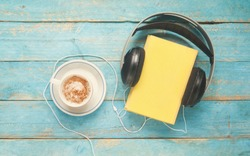 audio book concept, book, headphones and coffee, flat lay on old blue table, vintage image style