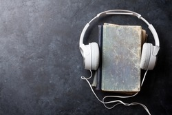 Audio book concept. Headphones and old books over stone table. Top view with space for your text