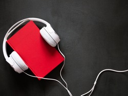 Audio book concept. White headphones and a red book on a stone black desk. Flat lay, top view, copy space