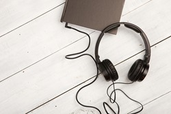 Audio book concept with black book and headphones on white wooden background