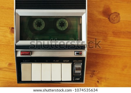Audio cassette tape rolling in vintage player on the desk, top view. Police interrogation sound recording retro technology concept for 1970s, 80s and 90s.