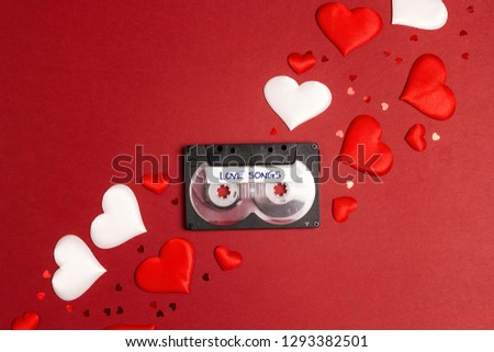 Audio cassette tape with love songs and hearts on red  background. Romantic mood music concept. St. Valentines Day. Flat lay, top view.   #1293382501