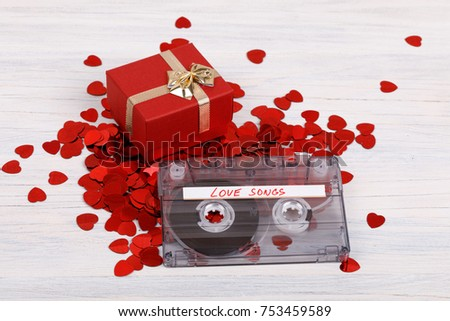 Audio cassette tape with present box, label text love songs on wooden background. #753459589