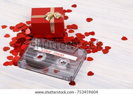 Audio cassette tape with present box, label text love songs on wooden background. #753459604