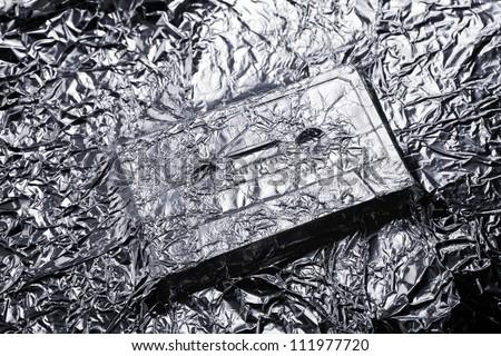 Audio compact cassette covered with aluminium foil.