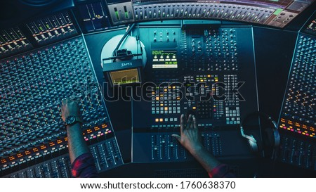 Audio Engineer, Musician, Artist Works in the Music Record Studio, Control Desk Mixer with Equalizer. Hand Moving Fader, Buttons to Broadcast, Record, Play Song. Neon Colors. Top Down View Foto stock ©
