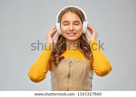 audio equipment and technology people concept - smiling teenage girl in headphones listening to music over grey background