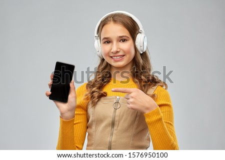 audio equipment and technology people concept - smiling teenage girl in headphones listening to music and showing smartphone over grey background