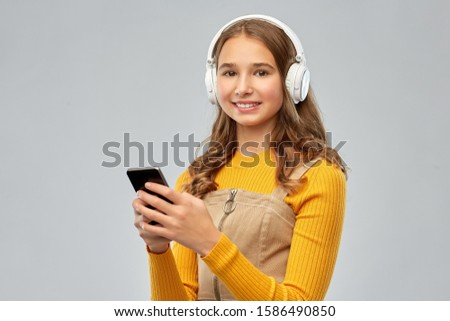 audio equipment and technology people concept - smiling teenage girl in headphones listening to music on smartphone over grey background