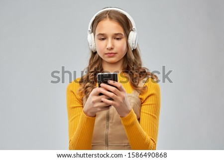 audio equipment and technology people concept - teenage girl in headphones listening to music on smartphone over grey background