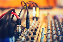 audio jack and wires connected to audio mixer, music dj equipment at concert, festival, bar