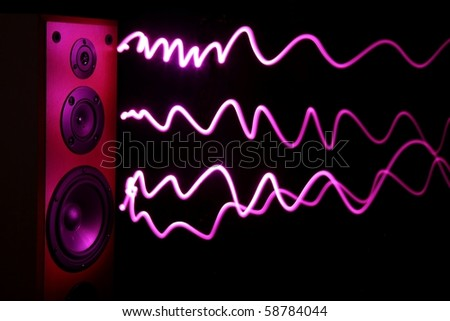 Audio speakers in a wooden cabinet with light effect for sound waves