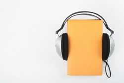 Audiobook on white background. Headphones put over yellow hardback book, empty cover, copy space for ad text. Distance education, e-learning concept