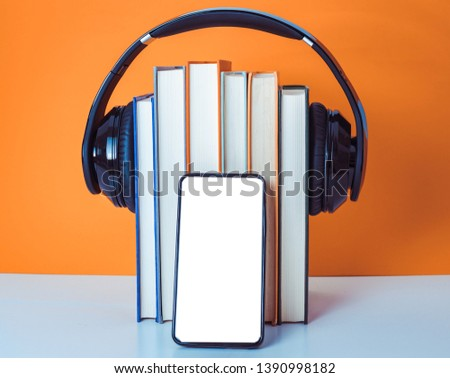 Audiobooks concept. Headphones put over book on orange and white background. Smart phone. Mobile phone.Front view copy space